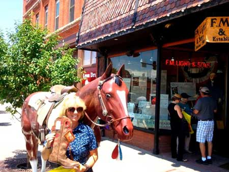 Customer Cathy Posing with her new Cowboy Boots and Lightning the Horse outise F.M. Light and Sons - Western Wear Store in Steamboat Springs, CO