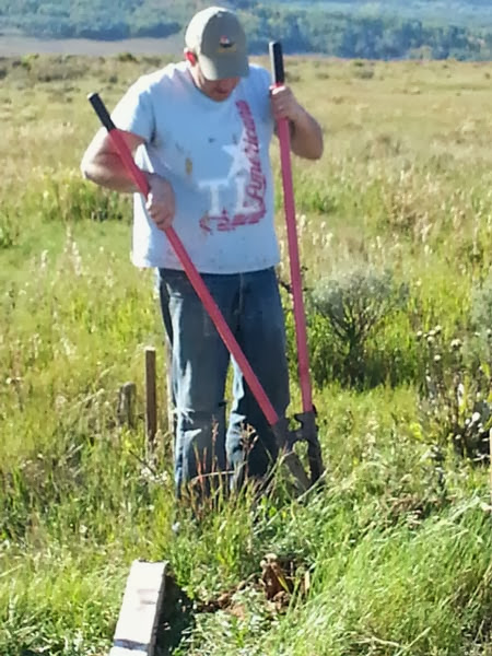 Chris Dillenbeck from F.M. Light digging fence post holes for a yellow road sign.